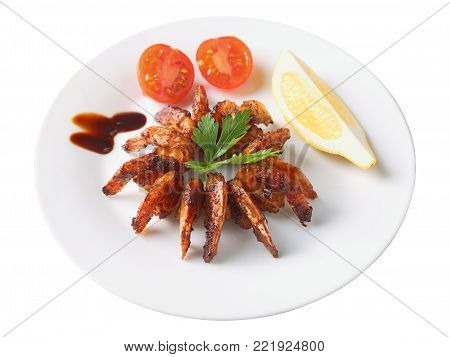 shrimps roasted in teriyaki sauce with  slice of lemon and cherry tomato on a white round dish isolated on white background. Inclined view.