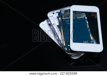 disassembled smartphone on black background. technical specifications of mobile devices and other gadgets. microelectronics technology
