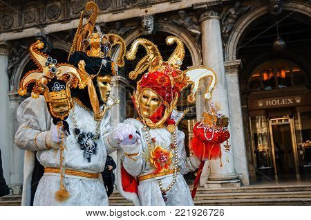 VENICE, ITALY -  FEBRUARY 27, 2014: Carnival of Venice. Two people in beautiful carnival costumes and traditional masks take walk on old street.