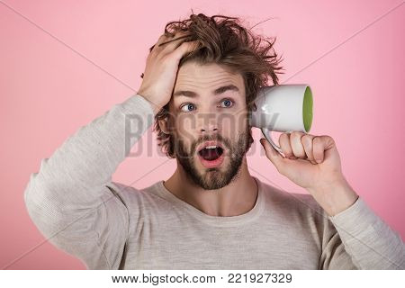 surprised man with disheveled hair hold coffee cup at ear in morning on pink background, flu and cold, hangover and insomnia, gossip