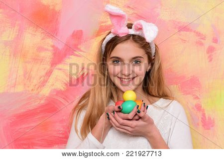 happy easter, traditional spring holiday celebration. girl in pink bunny ears with colorful painted eggs, has long blonde hair and adorable smiling face on abstract background, copy space