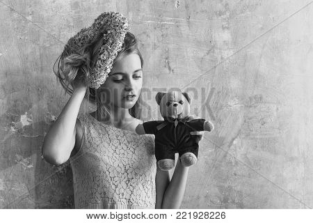 Pretty girl or cute woman with blond hair and adorable face in yellow dress with teddy bear toy and pink wicker heart for valentines day on textured wall background, copy space