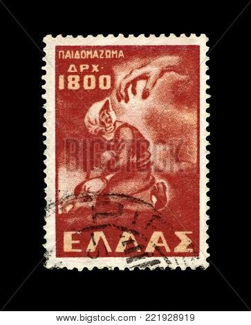 GREECE - CIRCA 1949: vintage canceled stamp printed in Greece shows protective mother near concentration camp, circa 1949. vintage postal stamp isolated on black background.