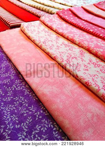Color fabric patterns, cotton colored samples, variety of species in the background.