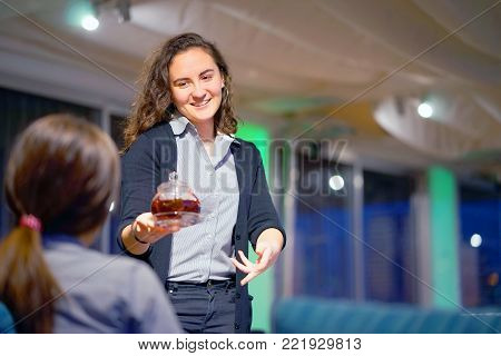 The waitress is carrying tea. Hospitable girl waitress is carrying tea and tea glass teapot to the client in the hotel restaurant. The concept of maintenance and service.