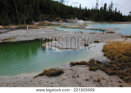 Near grand prismatic spring are many hot pools, colored by minerals