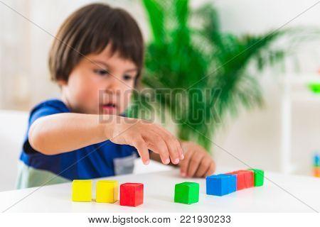 Child psychology, little boy stringing beads, color image