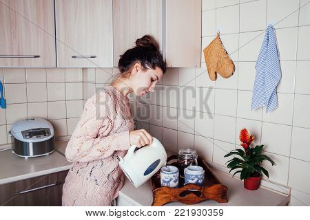 Young woman preparing tea for two in the kitchen. Pouring water into a cup.