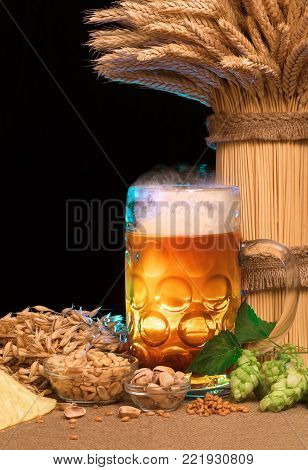 beer, hops, snacks, ingredients for making beer and sheaf of wheat on the table, dark background