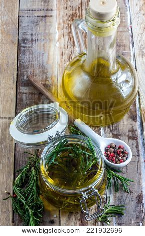 Olive oil rosemary flavored in glass bottle, mix of peppercorns in a ceramic spoon and branches of plant rosemary on rustic wooden background. Selective focus