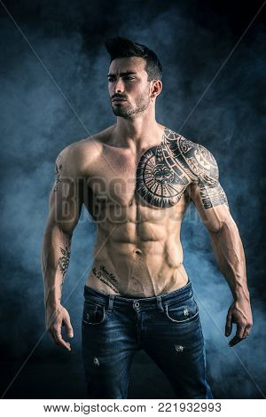 Handsome shirtless muscular man with jeans, standing, on dark smoky background in studio shot