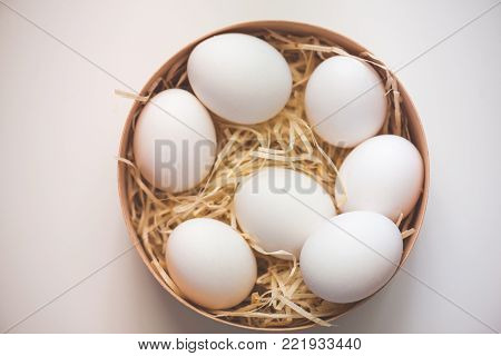 Close-up view of raw chicken eggs in egg box on white background
