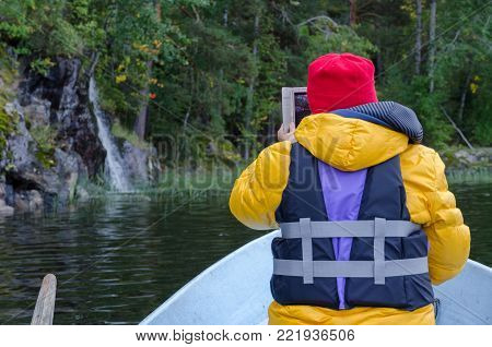 A woman is wearing a life jacket and is sitting in a boat. She takes pictures of the beach with a waterfall. The shore of the lake is covered with forest.