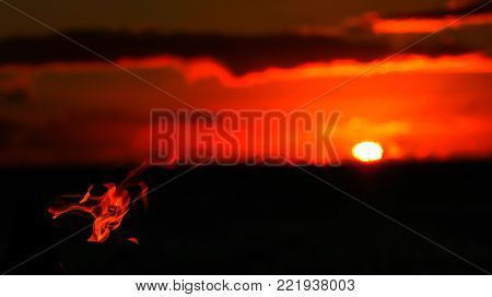 Torch flame blows horizontally before sunset on horizon
