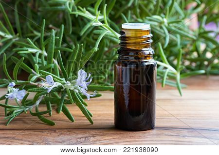 A dark bottle of rosemary essential oil with fresh blooming rosemary twigs on a wooden background