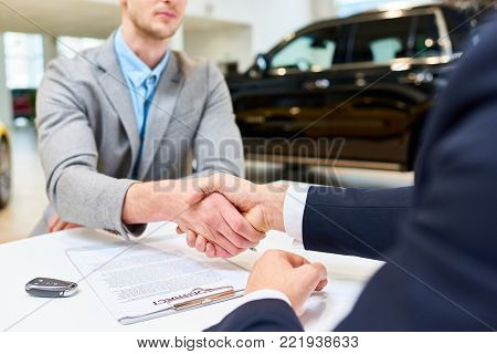 Close up of handsome client shaking hands with sales manager after signing purchase contract to buy new car in showroom