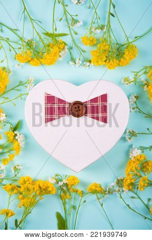 Gift box in form of heart surrounded with yellow little flowers on light mint background. Spring present with flower frame.