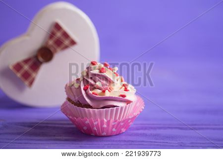 Cupcake With Creamy Pink And White Top Decorated With Little Hearts On Purple Background