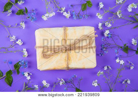Wrapped Paper Gift Box Surrounded With Blue And White Little Flowers On Purple Background