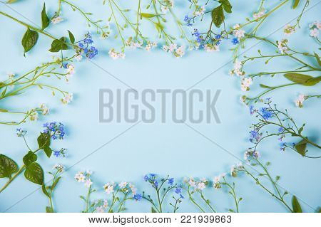 Spring frame made from little blue and white flowers on light mint background. Seasonal blooming card with empty space.