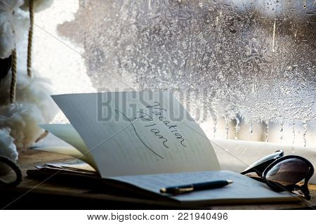 National plan your vacation day conceptual background for hashtag #planforvacation notepad on winter window with frosted glass winter scenery and crystals on desk with list and words Vacation plan written