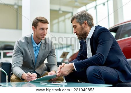 Portrait of handsome young man signing purchase contract buying new car in luxury showroom, sitting at table with mature salesman