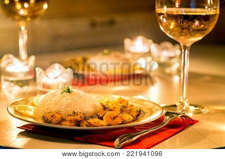 Close up of prawn with rice and bottle of white wine. Seafood dinner. Romantic supper. Love date or Valentine's Day concept