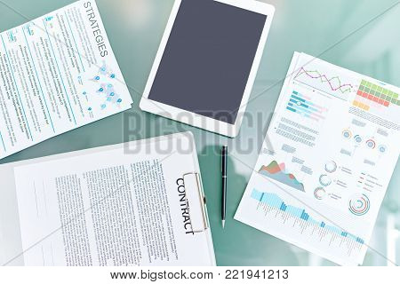Above view background composition of documents and digital tablet on glass table, contract, marketing strategies plan and  statistic graphs.