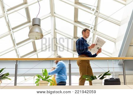 Low angle portrait of young businessman wearing casual clothes reading newspaper standing at balcony in modern office building under glass roof