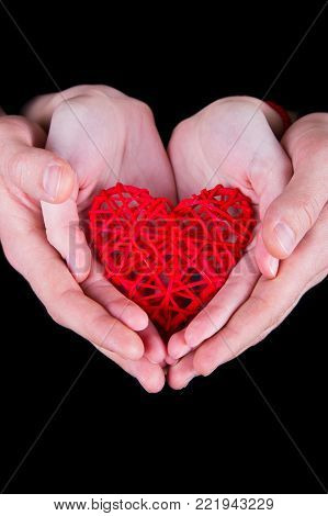 Two pairs of adult hands holding red wicker heart on black background. St. Valentine card.