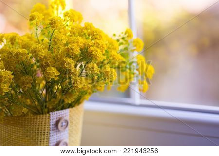 Lush yellow bouquet of little tender flowers near window. Spring composition in daylight.