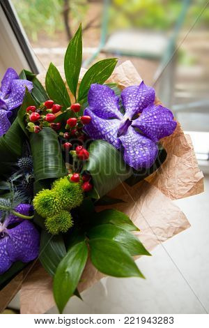 Decorative bouquet with purple orchids in kraft paper near the window. Spring composition in daylight.