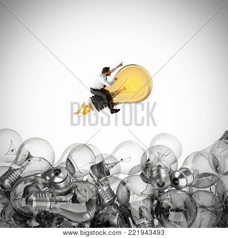 Businessman rides a bright bulb lit between unlit bulbs. Successful and intelligent idea. 3D Rendering