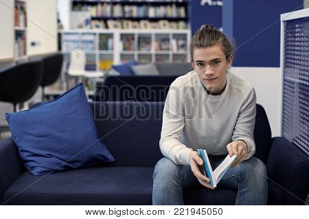 Handsome university student in sweater and jeans using wireless headset while listening to information, preparing for test in college. Cute guy enjoying music in headphones, having dreamy look
