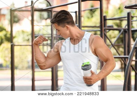 Handsome young man with protein drink in shaker outdoors