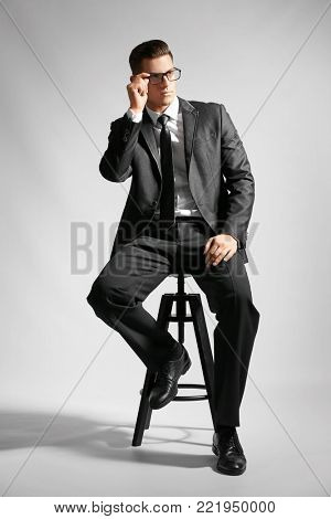 Handsome man in elegant suit sitting on chair against light background