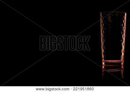 Faceted empty glass of water with fire reflection isolated on a black background. Place for your text.
