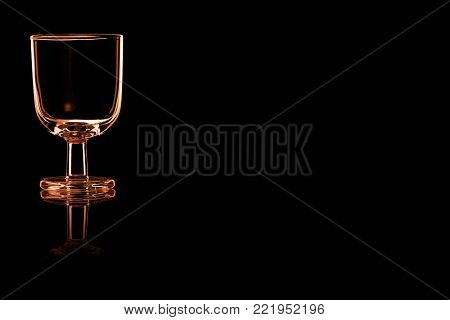 An empty glass of port or sherry with fire reflection isolated on a black background. Place for your text.