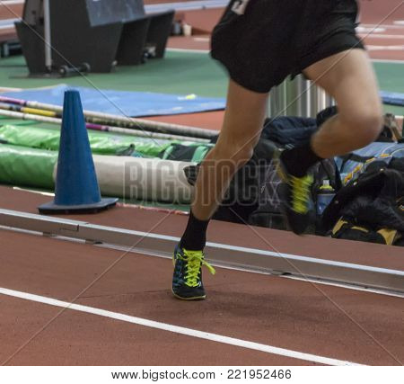 A high school track runner getting up on his toe on an indoor track finighing his race with a srint kick.