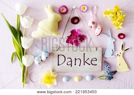 Wooden Sign With German Text Danke Means Thank You. Easter Flat Lay With Decoration Like Easter Bunny And Easter Egg. Spring Flower Blossoms Like Tulipa, Daisy And Narcissus.