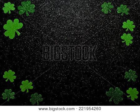 Different green colored shamrocks of various sizes on a shiny black background