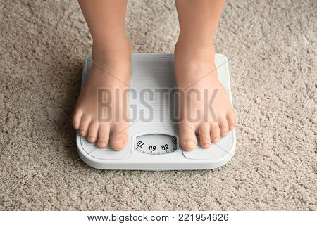Overweight boy using scales at home