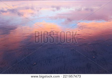 Pink clouds reflection in wet sand of Kuta beach, Bali, Indonesia