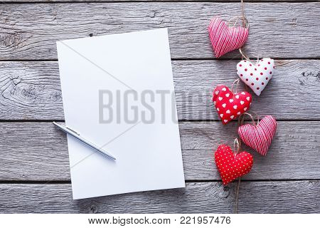 Valentine confession letter background with diy sewed pillow hearts bunch on clothespins at rustic gray wood planks, copy space Valentine's Day, love, romantic concept. Horizontal orientation