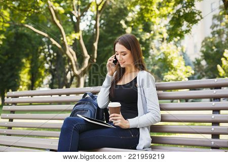 Smiling young woman talking on mobile, working on laptop and having coffee, sitting in park on bench. Technology, education and remote working concept, copy space