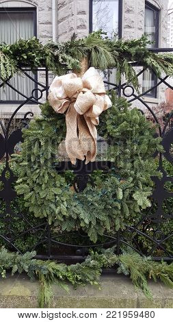 Green Christmas Holiday Wreath with a Gold Bow adorning a black metal fence in winter
