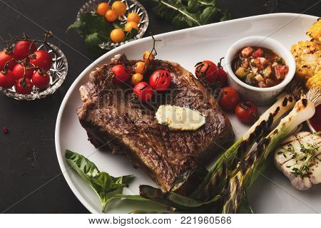 Restaurant dish background. Juicy medium beef steak with sauce and grilled vegetables. Healthy exclusive food on big white platter closeup