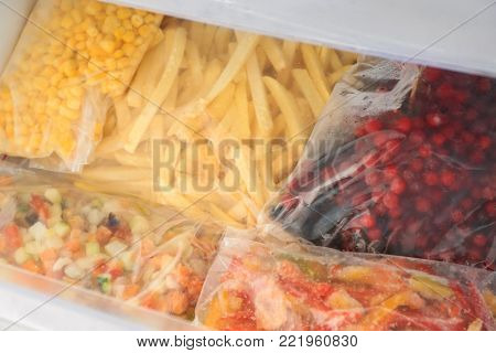 Plastic bags with different food in refrigerator