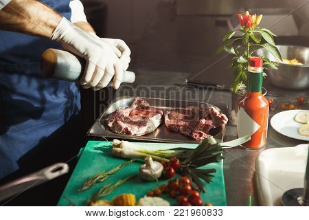 Unrecognizable male chef in gloves preparing vegetable salad, seasoning lettuce leaves with olive oil in professional hotel or restaurant kitchen interior