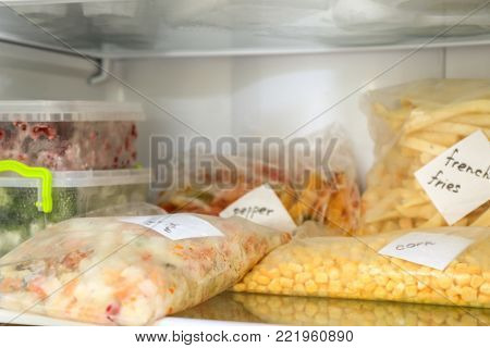 Plastic bags and containers with different food in refrigerator